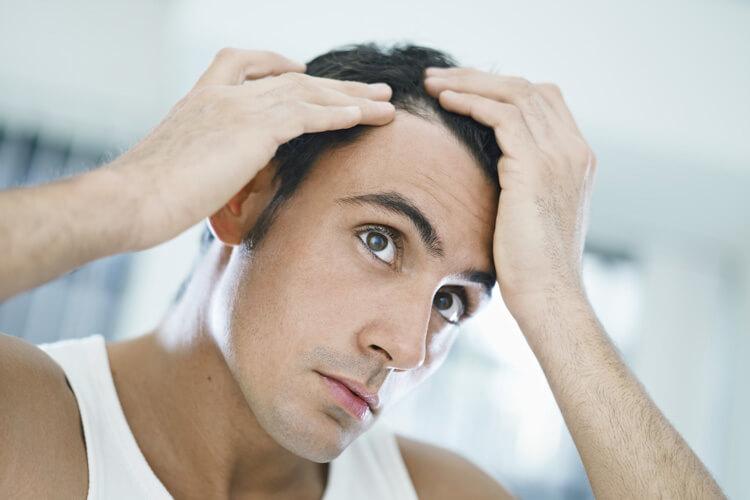 Uomo che si controlla i capelli